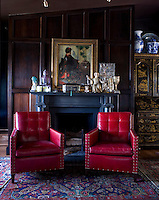 The dark wood panelled library features a pair of red leather armchairs with a collection of 1830s Russian objects displayed on the mantelpiece