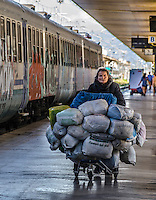Urban Street Photography. Termini station in Rome Italy. <br /> A photograph of a lady pushing her shopping  cart filled with bags, and the train that is covered in graffiti speak of lifestyles that do not conform to the mainstream of life.