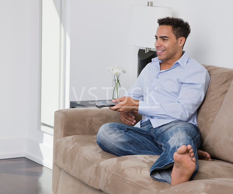 USA, New York State, New York City, young man watching television on sofa