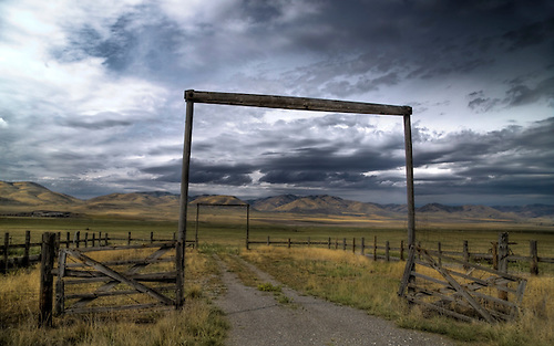 An old road leads to a Utah farm pasture under threatening skies.