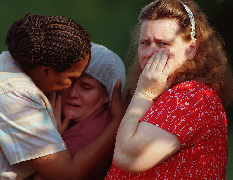 Bystander Amanda Smith, left, of West Springfield comforts Elaina Kuropatkin, as Marina Kuropatkin looks on as police and EMTs attend to two drowning victims in West Springfield on Thursday, July 15, 1999. Photo by Christopher Evans