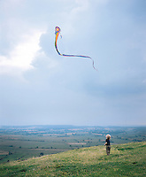 2 year old Lucas watches a kite flying on top of the Glastenbury Tor which overlooks the lush Somerset landscape.  UK 06-2002