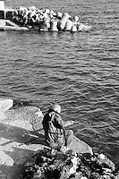 Castro Marina - Salento - Puglia - Pescatore intento a pescare vicino al porto. Sullo sfondo si notano i frangiflutti in cemento.
