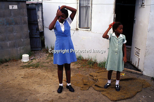 dippchi00281 Children. Sisters combing their hair before going to school on July 22, 2001 in Site B Khayelitsha, a township about 35 kilometers outside Cape Town, South Africa. Khayelitsha is one of the poorest and fastest growing townships in South Africa.  Early morning.©Per-Anders Pettersson/ iAfrika Photos.