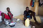 Two boys have lunch in a hut in Cateme village, a Vale resettlement compound with over 700 families from the villages of Chipanga, Mitete, Malabue-Gombe and Bagamoyo. All houses are constructed equally with no respect to the inhabitants' needs. The boys live in what was supposed to be the kitchen and cooking is now moved outdoors. ??Vale deliberately divided the communities in two with employed villagers moving to 25 de Setembro since it is closer to Moatize and the coal mine. The unemployed were resettled to Cateme, 40 km from the original town. While the most immediate problem of the community is the enormous distance to Moatize, their old habitat, they also suffer from unproductive farmland which can only be reached via a two hour walk, no access to markets and infrastructure and poorly constructed houses not fitted to the people's needs with temperatures inside reaching as high as 65° C due to the construction with tin clad roofs and missing isolation.