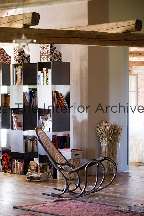 A traditional rocking chair in front of a wall of modern metal bookcases in the open-plan living space