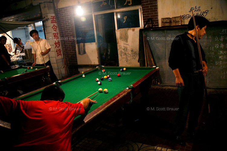 People play pool at an outdoor pool hall in Nanjing, China.