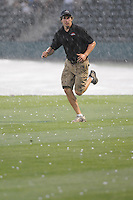 A member of the Greenville Drive grounds crew runs for cover as hail hits the field during a rain delay before a game on May 26, 2011, at Fluor Field at the West End in Greenville, S.C. The game was postponed due to rain. (Tom Priddy / Four Seam Images)