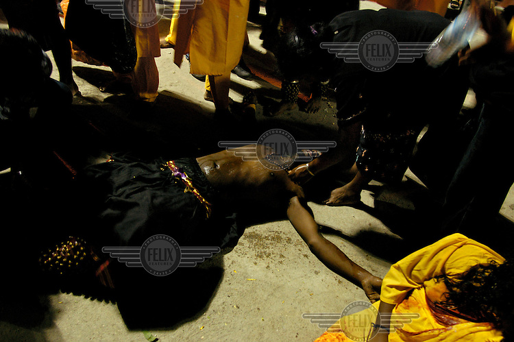 An ethnic Tamil man lies on the ground having lost consciousness after a ritual release from his trance-like state, achieved at the climax to his pilgrimage for the Thaipusam festival.  The annual Tamil Hindu festival of penance and thanksgiving commemorates the birth of Hindu Lord Murugan and his triumph over evil. Pilgrims engage in various acts of devotion such as carrying burdens, flagellation and body piercing as they take part in a 15-kilometre procession to the Batu Caves. .