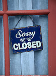 Old fashioned 'Sorry we're Closed' sign in window of closed down village shop