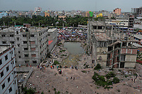 Bangladeshi family members of victims of Rana Plaza building collapse, stand at the site of the accident along with activists and journalists in Savar, near Dhaka, Bangladesh.