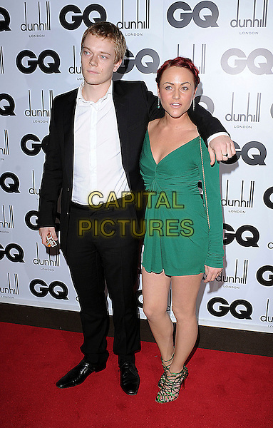 ALFIE ALLEN & JAIME WINSTONE .attending the GQ Men Of The Year  Awards 2008, Royal Opera House, London, England, .2nd September 2008..inside arrivals full length green long sleeved dress black suit jacket white shirt shoes strappy arm around shoulder couple Jamie.CAP/BEL.©Tom Belcher/Capital Pictures