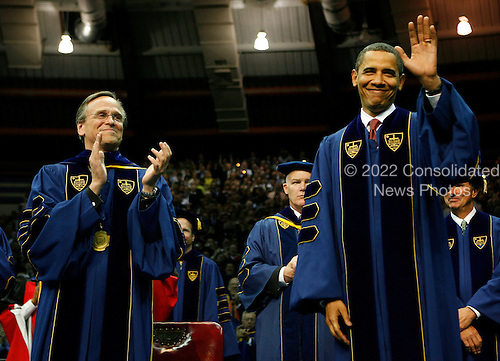 South Bend, IN - May 17, 2009 -- United States President Barack Obama waves to the crowd with University President Rev. John I. Jenkins (L) before the start of the 164th commencement ceremonies at the University of Notre Dame in South Bend, Indiana, May 17, 2009.  .Credit: Jeff Haynes / Pool via CNP