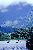Girls paddling kayaks on the Hanalei River with waterfalls of Mount Waialeale in background, Kauai, Hawaii