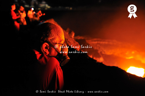 Senior man watching lava flowing to sea, night (Licence this image exclusively with Getty: http://www.gettyimages.com/detail/100378210 )
