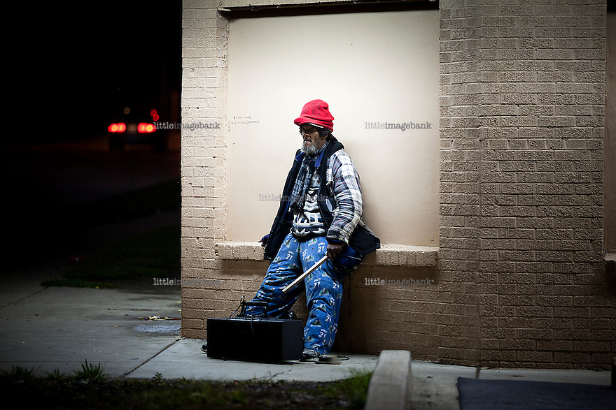 Pontiac, Michigan, USA. A homeless man is standing on a corner by a liques store in Pontiac. The state of Michigan once was concidered a promised land, in the era of the american automobile industry adventure. Due to the financial crisis, the state is on the brink of economic and social colapse. Fifty years ago, the city of Detroit was home of two million residents. In 2012 only 700.000 residents remain, and 87 percent of the remaining residents are African Americans. The gap between rich and poor in Detroit are as great as in the Philipines. Photo: Christopher Olssøn.