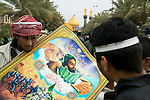 Pilgrims look at a poster on sale depicting the Tragedy of Karbala. Karbala, Iraq, 01.03.04
