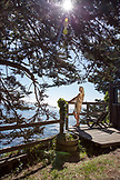 USA, California, Big Sur, Esalen, a woman enjoys the sun and the Pacific Ocean Views from the Point Houses deck, the Esalen Institute