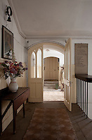 A view into the entrance hall through gothic double doors