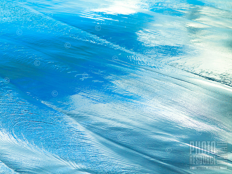As waves withdraw from the beach of Pololu Valley, the wet sand reflects the bright blue morning sky, Hawi, Big Island.
