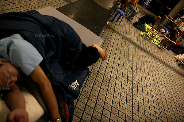 Members of the public now sleep at the pier to show solidarity. While this man sleeps, the protesters make banners and flags.<br /> <br /> In late May 2007, academics, students and members of the general public occupied Queen's Pier in central Hong Kong. They were protesting against the government's decision to demolish the pier to make way for a new development. The protesters were determined, but the odds were stacked firmly against them.