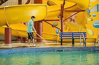 NWA Democrat-Gazette/ANTHONY REYES • @NWATONYR<br /> Jacob Carnes, lifeguard at the Jones Center, cleans the deck Tuesday, Sept. 8, 2015 around the leisure pool at the Jones Center in Springdale. The pool was recently refinished and is now open to the public during its regular pool schedule. A grand opening for the pool will be 10 a.m. on Friday.