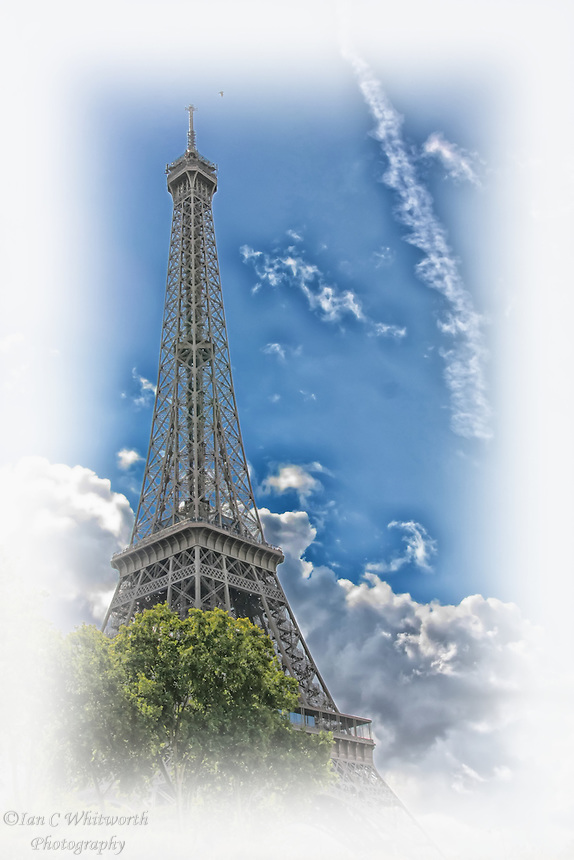 Looking up past the trees at the Eiffel Tower in Paris in a photo art style.