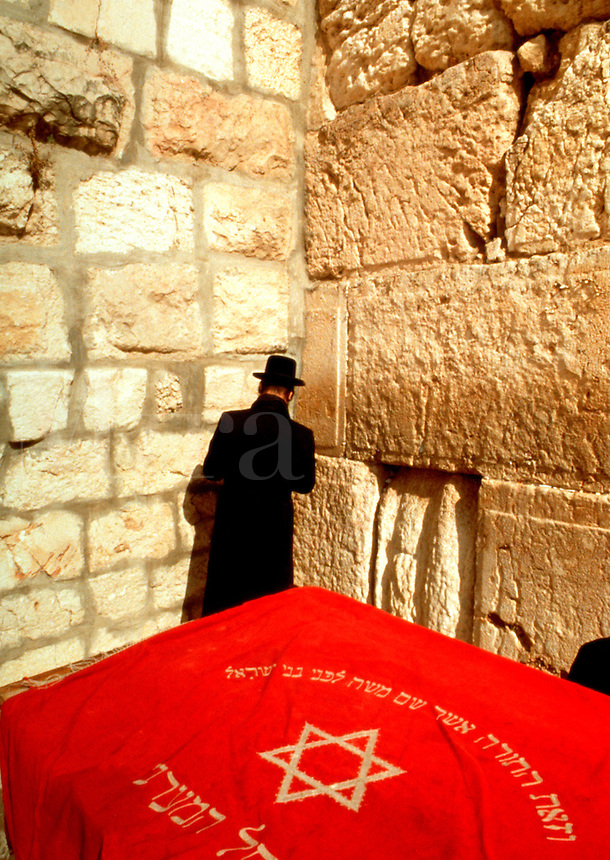A Hasidic Jewish man prays at the Western Wall; a cloth with a Star of David and Hebrew script in the foreground. Jerusalem, Israel.