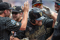 Vanderbilt Commodores outfielder Stephen Scott (19) is mobbed by his teammates after his second inning home run against the Mississippi State Bulldogs in the NCAA College World Series on June 19, 2019 at TD Ameritrade Park in Omaha, Nebraska. Vanderbilt defeated Mississippi State 6-3. (Andrew Woolley/Four Seam Images)