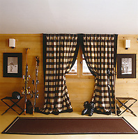 The ski boot room has a brown and cream check fabric against the window and a pair of wrought-iron leather stools picked up in Spain