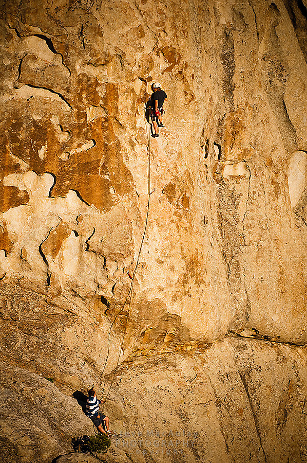 "Teenage boy rock climbing in the golden light of sunset at The City of Rocks, Idaho.  Route is named ""Scream Cheese""  rated 5.9"