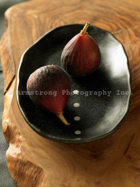 Two fresh figs in a black bowl on wooden slab