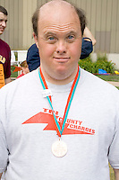 Athlete posing with summer games winning medal. Special Olympics U of M Bierman Athletic Complex. Minneapolis Minnesota USA
