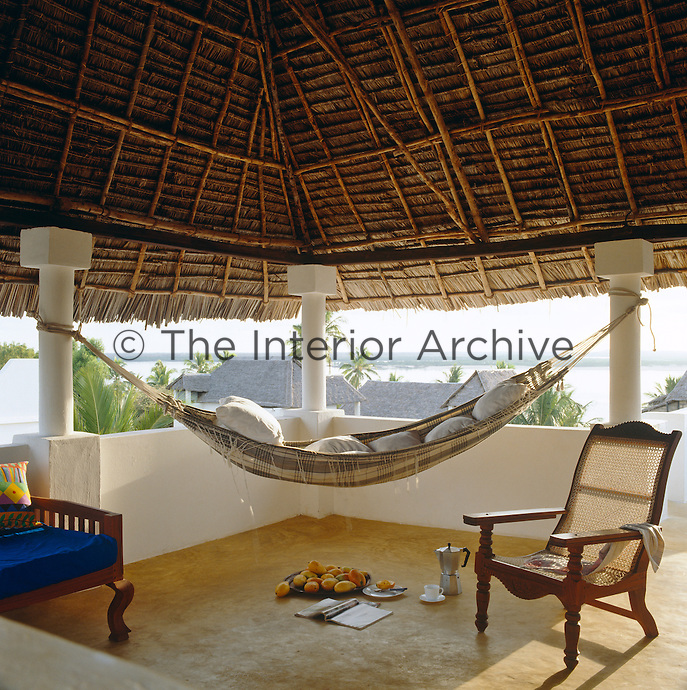 A hammock has been strung between two uprights that support the thatched roof of this terrace located at the top of the house to catch the breeze