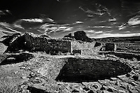 A black and white image of a kiva at Pueblo Bonito in Chaco Canyon National Historical Park with ruins in the background.