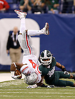 Ohio State Buckeyes running back Carlos Hyde (34) gets upended by Michigan State Spartans cornerback Trae Waynes (15) during the first quarter of the Big Ten championship football game at Lucas Oil Stadium in Indianapolis on Dec. 7, 2013. (Adam Cairns / The Columbus Dispatch)