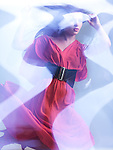 Futuristic dynamic high fashion photo of a young woman wearing a red dress in shiny neon light settings. The photo has a slight motion blur due to its nature. The photo was not digitally manipulated.