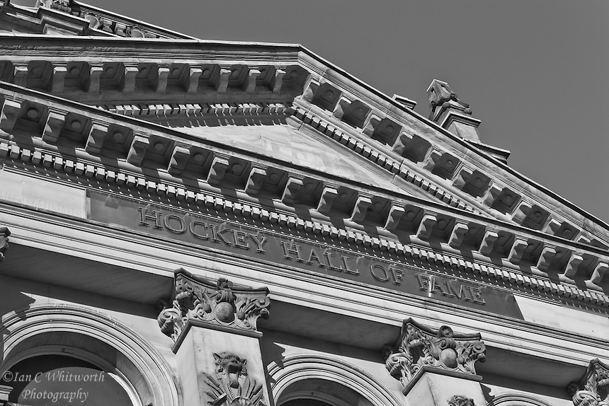 Looking up at a black and white view of the name and roof lines of the Hockey Hall of Fame in Toronto