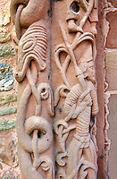 Norman Romanesque relief sculptures of mythical dragon and a man from the south doorway of the Church of St Mary and St David, Kilpeck Herifordshire, England. Built around 1140