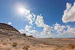 Desert landscape with mountains and sun star against cloudy blue sky in the Sahara desert of Morocco.