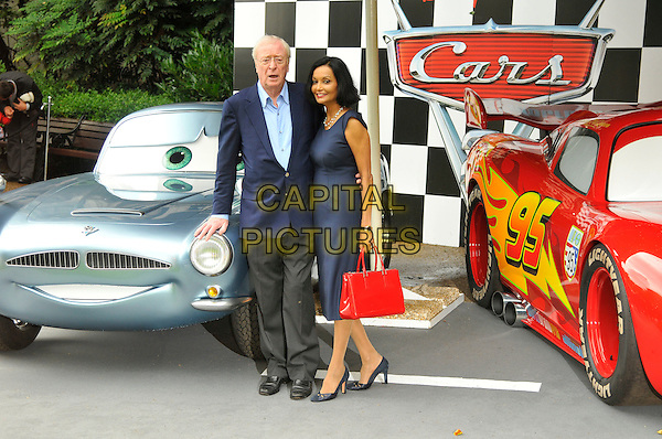 Sir Michael Caine & Shakira Caine.UK Premiere of 'Cars 2' at Whitehall Gardens,  London, England..July 17th 2011.full length black shirt blue suit jacket grey gray trousers blue dress married husband wife red bag purse.CAP/CAS.©Bob Cass/Capital Pictures.