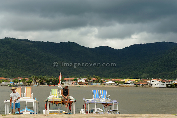 Local brazilian boatman in the small harbour waiting at their boats for tourists; Paraty, Espirito Santo, Brazil. The beautiful colonial town of Paraty has been a UNESCO World Heritage Site since 1958. --- No signed releases available.