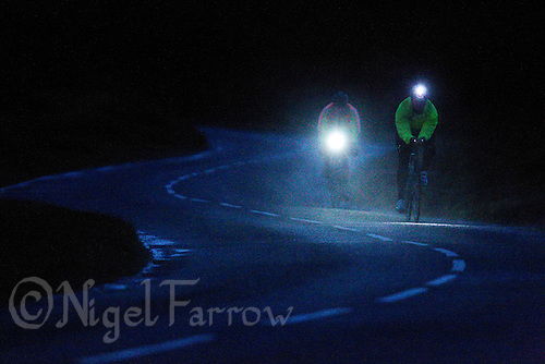 10 JUN 2011 - BRANSGORE, GBR - As the light fails competitors   continue to make their way around the bike course during the Triple Enduroman race at the Enduroman Ultra Triathlon Championships with lights on their bikes and helmets and, dressed in reflective jackets (PHOTO (C) NIGEL FARROW)