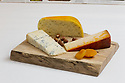Three pieces of cheese on a cutting board with apricots and hazelnuts