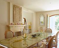 The table in the dining room beneath a glass top is decorated with a hand-painted gold motif that echoes the lines and colour of the gilded dining chairs