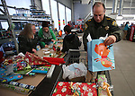 Carson City Sheriff Ken Furlong loads a cart with gifts after helping one of nearly 170 elementary students shop as part of the Holiday with a Hero program at Walmart in Carson City, Nev., on Tuesday, Dec. 17, 2013. The community event partners military, firefighters, law enforcement and medical personnel with local Students in Transition to provide them with Christmas presents.<br /> Photo by Cathleen Allison