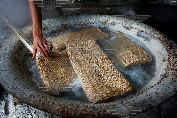 A labourer soaks woven material in heated water to soften it.