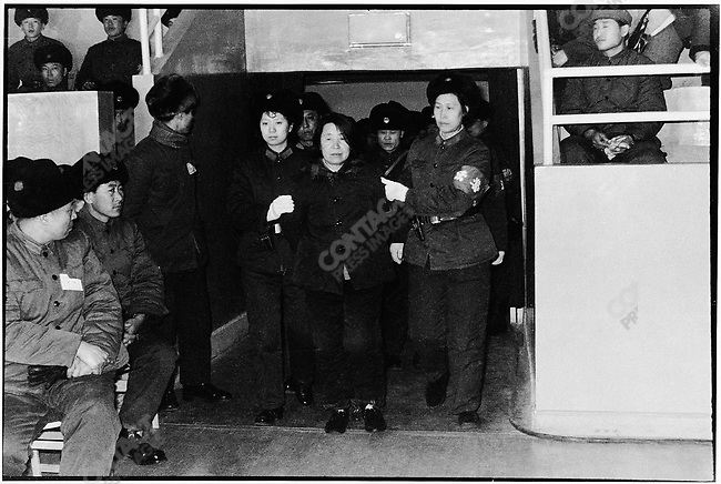 """Wang Shouxin, a former rebel and Party branch secretary during the Cultural Revolution, is hauled before a crowd of five thousand """"guests"""" at Harbin's Workers Arena to hear her sentence on charges of embezzlement. Harbin, 8 February 1980"""