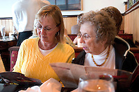 Guests reading a menu at the Salt Rock Grill which is located on The Narrows of the Gulf Intercoastal Waterway.  Indian Shores Tampa Bay Area Florida USA
