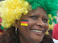 Germany, DEU, Dortmund, 2006-Jun-22: FIFA football world cup (USA: soccer world cup) 2006 in Germany; a female fan of the Brazilian football team wearing a wig in her national colours and a small German flag sticked on her cheek.